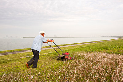 Man mowing the lawn - p834m1138372 by Jakob Börner