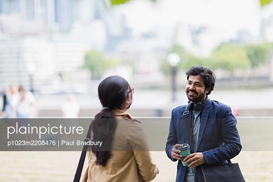 Business people talking in city park - p1023m2208476 by Paul Bradbury