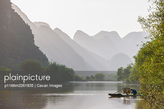 fisherman on traditional raft on the Yulong river close to Yangshuo - p1166m2261835 by Cavan Images