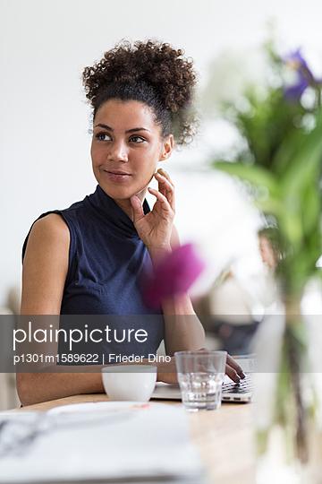 Hübsche Frau lächelt am Arbeitsplatz  - p1301m1589622 von Delia Baum