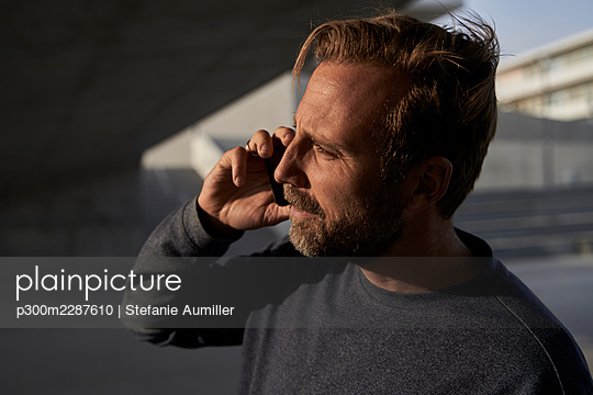 Male professional talking on mobile phone during sunny day looking away - p300m2287610 by Stefanie Aumiller