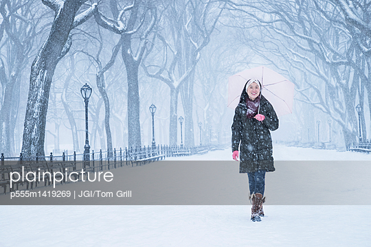 Asian woman walking in snowy Central Park, New York City, New York, United States