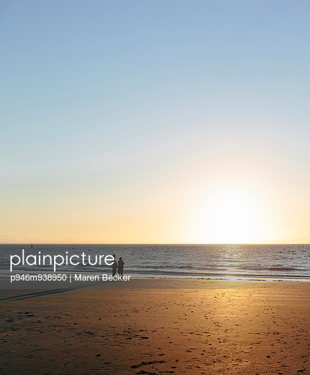 Paar schaut am Strand den Sonnenuntergang an - p946m938950 von Maren Becker