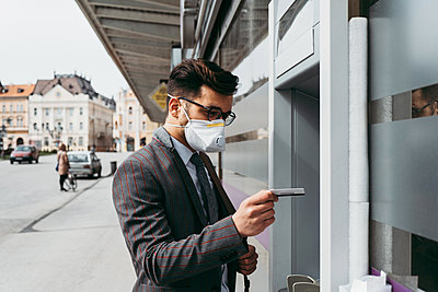 Business man with protective face mask using street ATM machine. - p1166m2179392 by Cavan Images