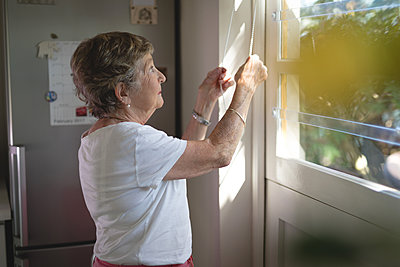 Senior woman opening window shade - p1315m1514669 by Wavebreak