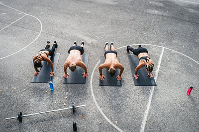 Sporty team during workout, pushups - p300m2069974 by Epiximages