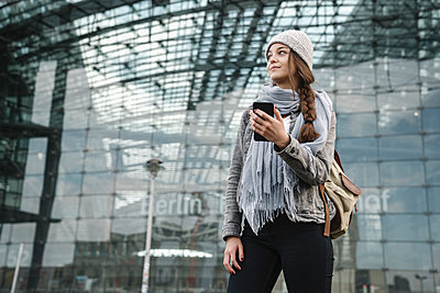 Young woman with smartphone waiting at the central station, Berlin, Germany - p300m2154516 by Hernandez and Sorokina