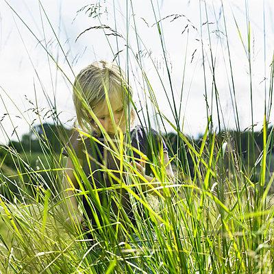 Girl hiding behind tall grass - p42916708f by Henrik Weis