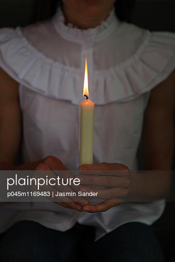 Frau hält Kerze in Händen - p045m1169483 von Jasmin Sander