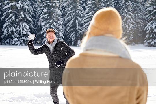 Junges Paar macht eine Schneeballschlacht - p1124m1589324 von Willing-Holtz