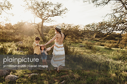Beautiful mother and young children playing in sunny field - p1166m2131205 by Cavan Images