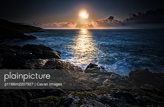 Setting Sun, Overlooking Rocks And Headland - p1166m2207927 by Cavan Images