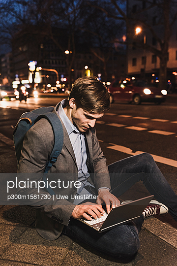 Businessman using laptop on urban street at night - p300m1581730 von Uwe Umstätter