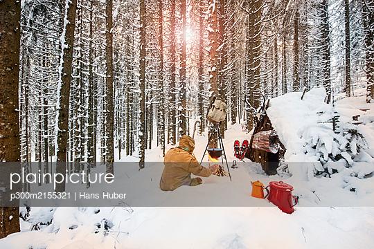 Man preparing tea in winter forest next to a wooden shelter, Salzburg State, Austria - p300m2155321 by Hans Huber