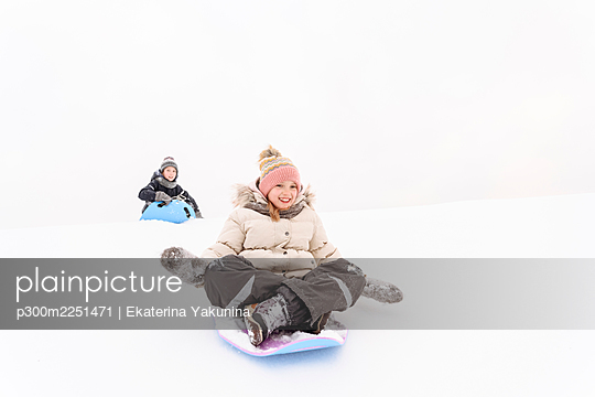 Playful siblings sledding on snow covered hill - p300m2251471 by Ekaterina Yakunina