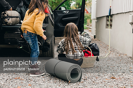 Sisters loading luggage in electric car trunk while going for picnic - p426m2195235 by Maskot
