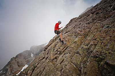 Side view of hiker using rope while climbing rock formations against clouds - p1166m1531499 by Cavan Images