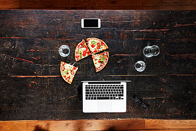 Laptop, smartphone, pizza and water glasses on tabletop, top view - p300m1562941 by Jo Kirchherr