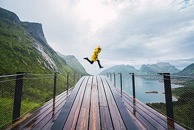 Norway, Senja island, man jumping on an observation deck at the coast - p300m2042288 by Kike Arnaiz