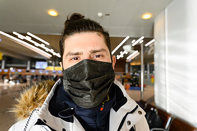 Male tourist at illuminated airport during pandemic - p300m2251638 by Ekaterina Yakunina