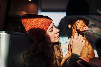 Madrid, Spain. Woman and her dog enjoy the sunlight entering her van. - p300m2293973 von Manu Reyes