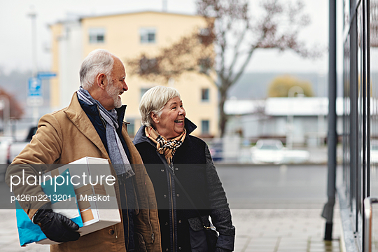 Smiling senior couple with package in city during winter - p426m2213201 by Maskot