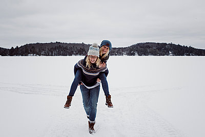 Cheerful woman piggybacking friend on snow during winter - p1166m1567602 by Cavan Images