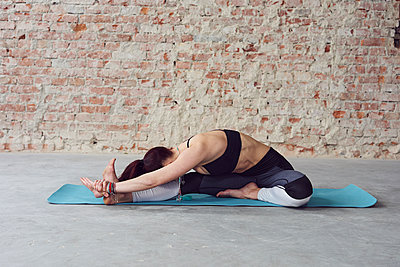 Young female in yoga pose by the brick wall - p1166m2095576 by Cavan Images