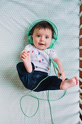 Portrait of baby girl lying in crib listening music with headphones - p300m1459724 by Gemma Ferrando