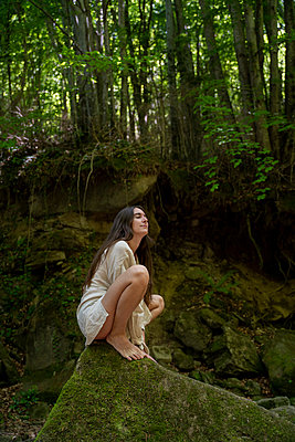 Young woman sitting on a rock in the forest, Garrotxa, Spain - p300m2113803 by VITTA GALLERY