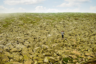 Caucasian hiker standing with arms outstretched in rocky field - p555m1414508 by Aleksander Rubtsov