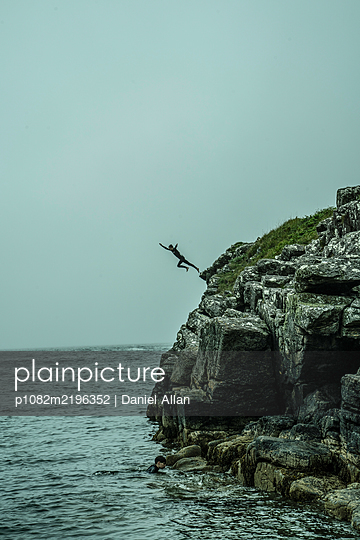 Teenage boy jumps from cliff into the sea - p1082m2196352 by Daniel Allan