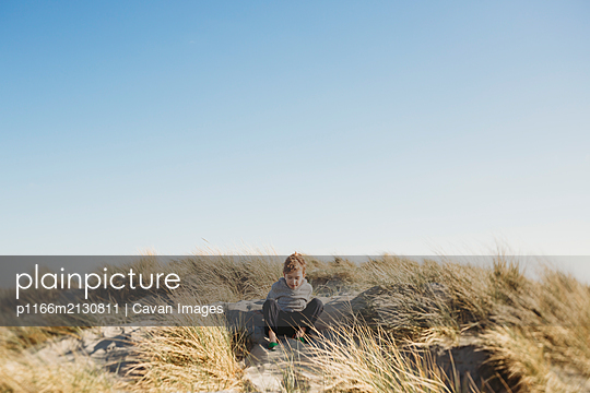 Low angle view of boy sitting on sand dune against clear blue sky - p1166m2130811 by Cavan Images