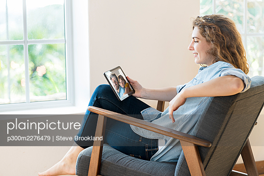 Smiling relaxed woman talking on video call through digital tablet while sitting on armchair in living room - p300m2276479 by Steve Brookland
