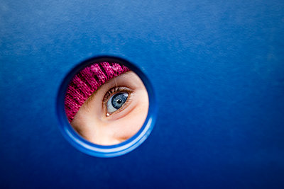 blue eye of a toddler girl through circle shape at playground at fall - p1166m2073713 by Cavan Images