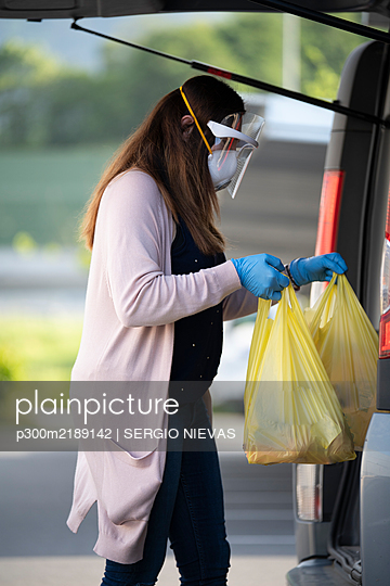 Side view of customer holding plastic bags by vehicle trunk at supermarket parking lot - p300m2189142 by SERGIO NIEVAS