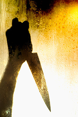 Knife silhouette seen through a wet window - p1228m2142782 by Benjamin Harte