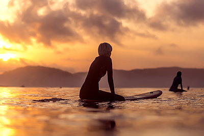 Female surfer in sea at sunset - p343m1585395 by Konstantin Trubavin