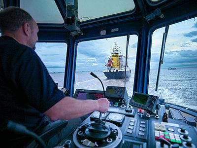 Worker driving tugboat in wheelhouse - p429m747059f by Monty Rakusen