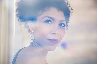 Mixed race woman wearing evening gown and earrings - p555m1413038 by JGI/Jamie Grill