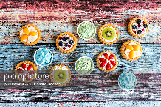 Mini pies with whipped cream garnished with different fruits - p300m1494773 by Sandra Roesch