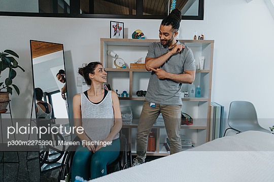 Smiling male physiotherapist pointing at elbow while explaining patient in medical practice - p300m2275990 by Mareen Fischinger