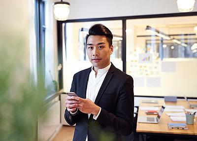 Asiatischer Mann mit Smartphone im Büro - p1124m1181500 von Willing-Holtz