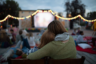 Affectionate mother and daughter at movie in the park - p1192m2024252 by Hero Images