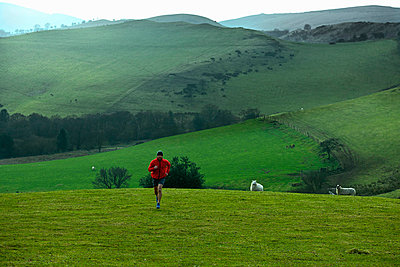 Man running in rural hills - p42914167f by Ross Woodhall