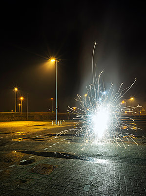 Fireworks going off in a car park, on new years eve, Heerenveen, Friesland, Netherlands - p429m1561648 by Mischa Keijser
