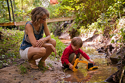 Caucasian mother watching son playing with construction toys in river - p555m1304045 by Christopher Winton-Stahle