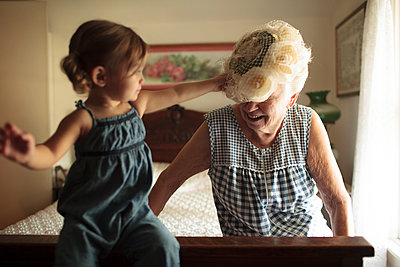 Grandmother and granddaughter playing on bed - p555m1408677 by Shestock