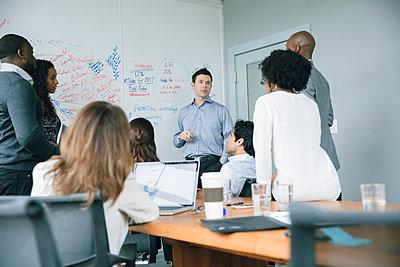 Businessman talking near whiteboard in meeting - p555m1504101 by John Fedele