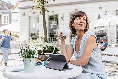 Woman in sidewalk cafe using tablet computer - p586m1171807 by Kniel Synnatzschke